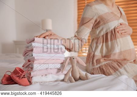 Woman With Stack Of Girl's Clothes And Booties In Bedroom, Closeup