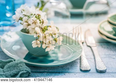 Place setting with blooming cherry branch in maritime blue style. Kitchenware and table setting.