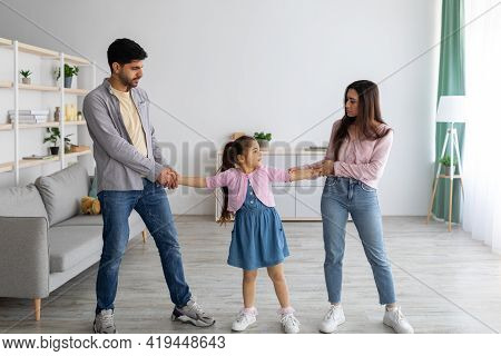 Divorce Concept. Arab Parents Fighting Over Their Child, Mad Man And Woman Quarrelling, Standing In