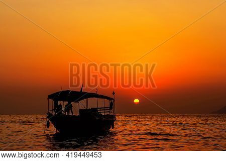 Boat And A Beautiful Sunset At The Sea On A Summer Evening