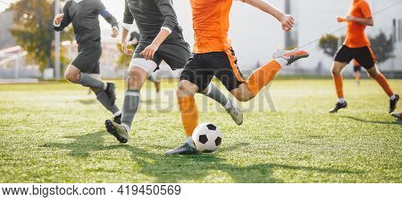 Group Of Football Players Running And Kicking League Match. Adult Football Players Compete In Soccer