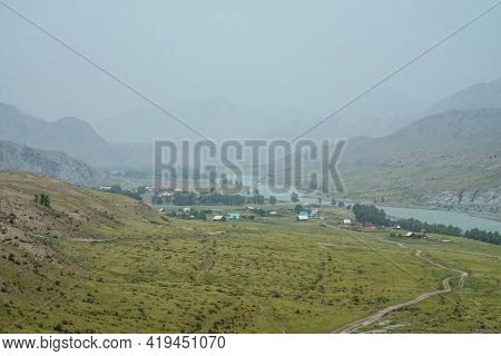 Scenic Alpine Landscape With Mountain Village By Mountain River In Mist. Atmospheric Misty Scenery W