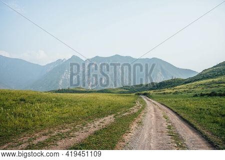Beautiful Green Mountain Landscape With Long Dirt Road And Big Mountains With Forest In Fog. Atmosph