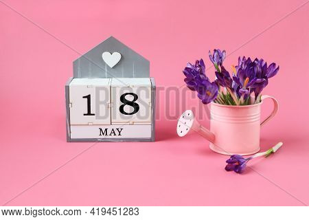 Calendar For May 18: A Cube With The Number 18, The Name Of The Month Of May In English,a Pink Water
