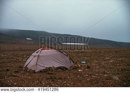 Atmospheric Misty Mountain Landscape With Tent In Stone Field In High Mountain Valley In Low Clouds.