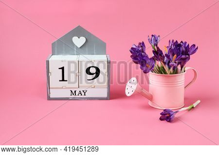 Calendar For May 19: A Cube With The Number 19, The Name Of The Month Of May In English,a Pink Water
