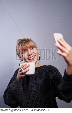 Morning Coffee And Making Selfie Concept. Young Caucasian Blonde Woman In Black Sweater Holding Cup