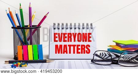 On The Table Are Colored Pencils In A Stand, Brightly Colored Stickers, Glasses And A Notebook With