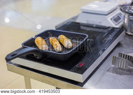 Process Of Cooking Chicken Rolls, Bangers, Sausages With Herbs In Frying Pan With Oil On Electric St
