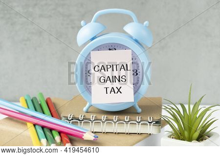 Holding A Card With Text Capital Gains Tax On Alarm Clock , Business Concept Image With Soft Focus B