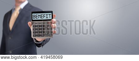 Calculator With The Word Benefit On The Display. Money, Finance And Business Concept. Businessman Sh