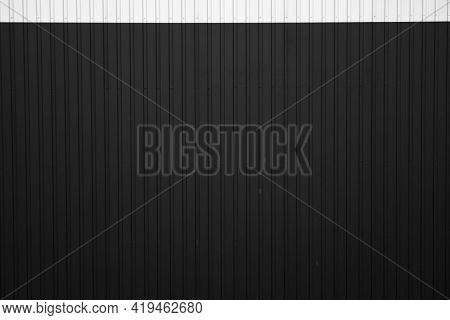 Black And White Corrugated Iron Sheet Used As A Facade Of A Warehouse Or Factory. Texture Of A Seaml
