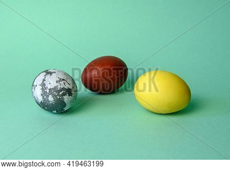 Three Eggs Painted With Natural Paint On A Green Neon Background. The Minimum Holiday Is Easter Or T