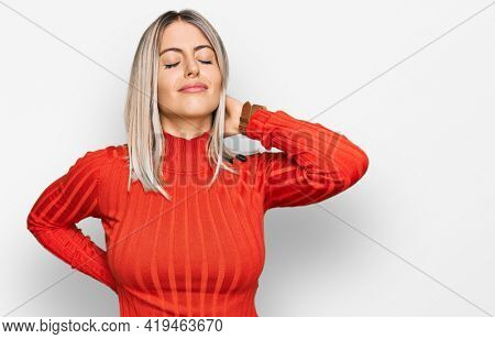 Beautiful blonde woman wearing casual clothes suffering of neck ache injury, touching neck with hand, muscular pain