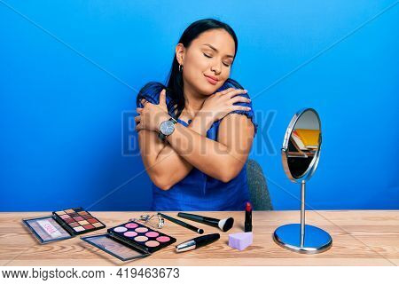 Beautiful hispanic woman with nose piercing getting ready using make up hugging oneself happy and positive, smiling confident. self love and self care