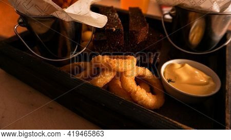 Beer Set Of Snacks On A Wooden Tray. Onion Rings And Sauces. Snack For Friends In A Brasserie