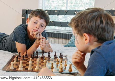 Two Boys Playing Chess At Home On The Bed. Friends Having Fun. Children Practice Playing A Board Gam