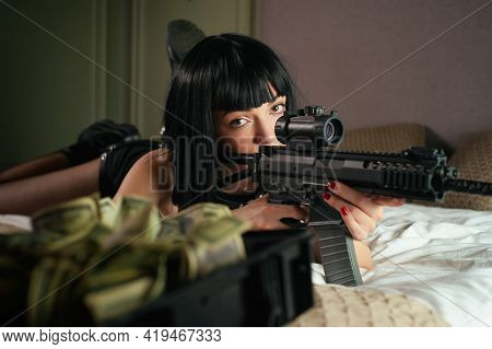 A Female Hitman In A Hotel Lies On A Bed And Holds An Automatic Rifle With A Telescopic Sight On The