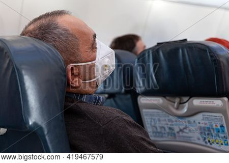 Russia Moscow 2021-03-01 Man Tourist In Face Medical Mask Sleeping In Airplane