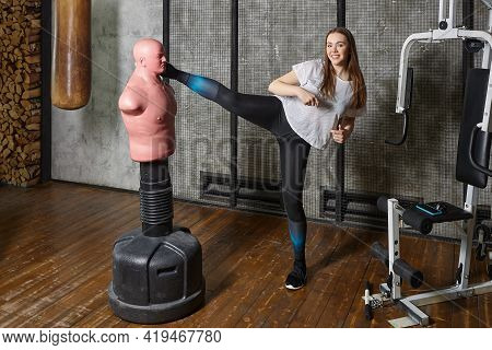 Body Opponent Bag Or Sparring Bob Helps Young Woman Workout In Gym.