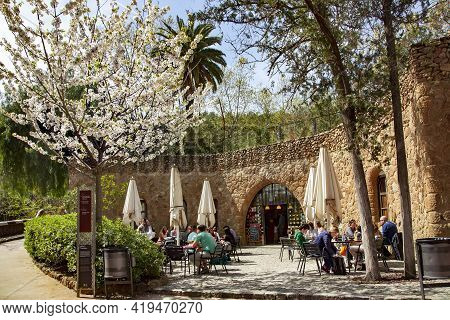Spain, Barcelona, March, 2021 - People Dine And Drink Coffee On The Open Veranda Of Cafes In Park Gu
