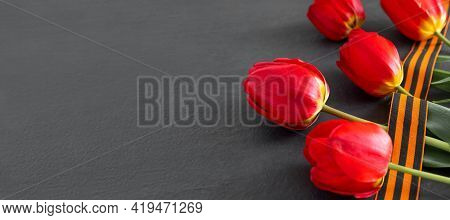 Happy Victory Day! May 9 Russian Victory Day. St. George Ribbon With Bouquet Of Red Tulips On  Black