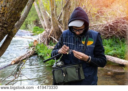 Young Angler Wearing A Vest And Warm Clothes Putting The Hooks On The Nylon And The Rod To Start Fis