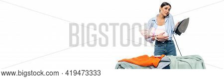 Discouraged Woman Talking On Mobile Phone While Holding Infant And Iron Isolated On White, Banner.