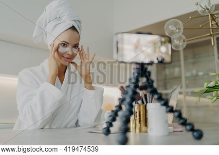 Female Beauty Blogger In Bathrobe Using Cosmetic Patches While Recording Video About Skin Care For H