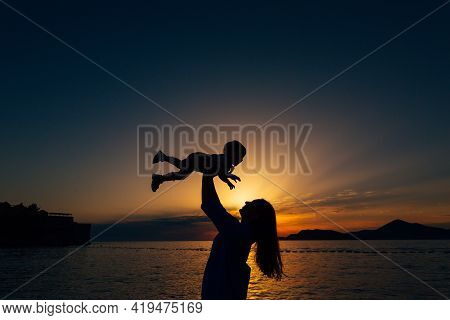 Mom Throws Up Her Little Son And Plays With Him On The Beach At Sunset