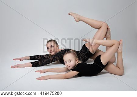 Mom And Daughter Athletes Gymnasts Demonstrate A Synchronized Pose