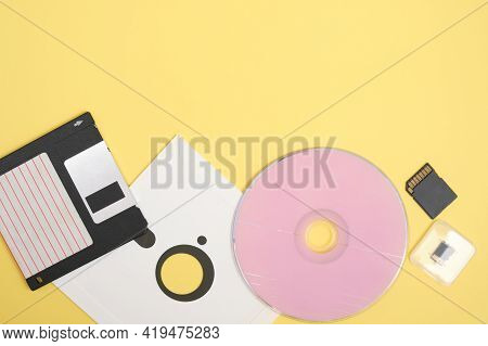 Various Types Of Disks For Storing Information On A Yellow Background, Modern And Retro Disks And Fl