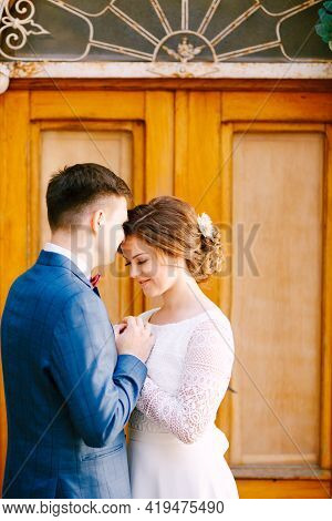 Groom Kisses Beautiful Smiling Bride Against The Background Of The Glazed Yellow Door. Groom Holds T