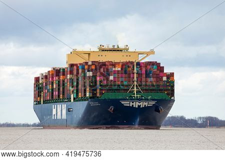 Stade, Germany – April 8, 2021: Container ship HMM Southampton, one of the 12 largest ships worldwide, on Elbe river heading to Hamburg