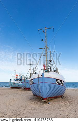 Thorup Strand, Denmark - August 30, 2020: Three fishing boats on the beach. Since the village has no harbor, the fishermen's cooperative  tows their boats onto the beach with tractors or winches.