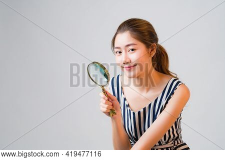 Asian Young Woman Using Magnifier Smile And Looking To Camera Over Grey Background. Concept Carefull