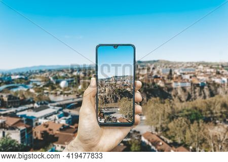 Georgia And Tbilisi Landscape. A Hand With A Smartphone Photographing The Sights Of Georgia And Tbil
