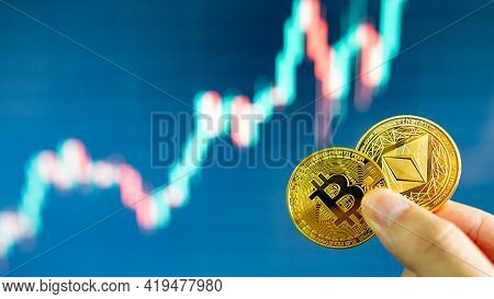 Hand Holding Gold Bitcoin And Ethereum With Blurred Candlestick Chart In The Background. Cryptocurre