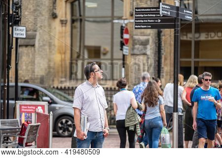 Traveler Reading Directions At Tourist Attraction Signpost With Direction Signs. Cambridge, Uk, Augu