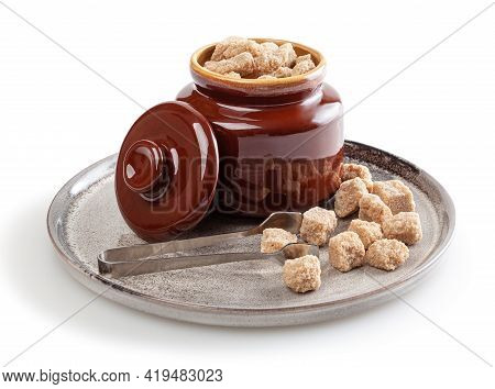 Cubes Of Brow Cane Sugar In Sugar Bowl On Ceramic Plate Isolated On White Background