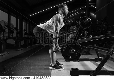 Handsome Young Man Pumps His Back In A Special Machine. Deadlifting. Fitness And Bodybuilding Concep