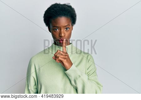 Young african american girl wearing casual clothes asking to be quiet with finger on lips. silence and secret concept.