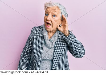 Senior grey-haired woman wearing wool winter sweater smiling with hand over ear listening and hearing to rumor or gossip. deafness concept.