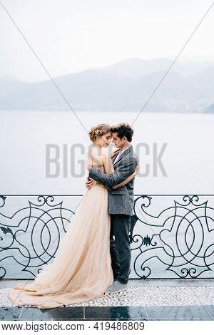 Newlyweds Hug Near A Wrought-iron Fence Against The Backdrop Of Lake Como