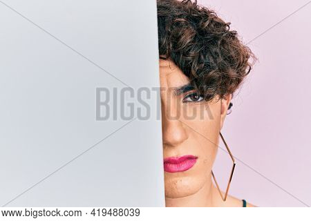 Young man wearing woman make up holding blank empty banner covering half face depressed and worry for distress, crying angry and afraid. sad expression.