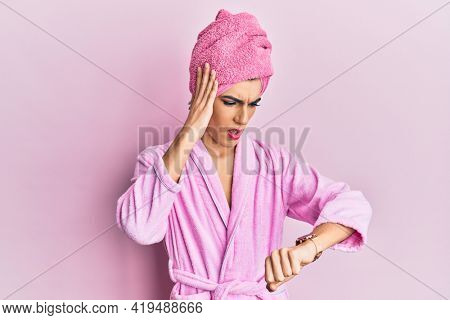 Young man wearing woman make up wearing shower towel on head and bathrobe looking at the watch time worried, afraid of getting late