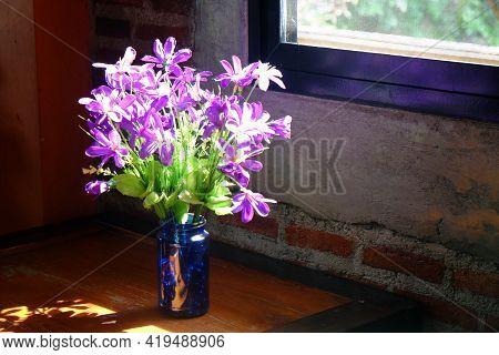 Purple Combretum Indicum, Aka Therangoon Creeper Orchinese Honeysuckle In Blue Glass Bottle On Woo