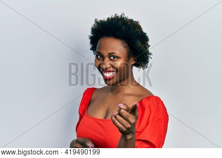 Young african american woman wearing casual clothes pointing fingers to camera with happy and funny face. good energy and vibes.