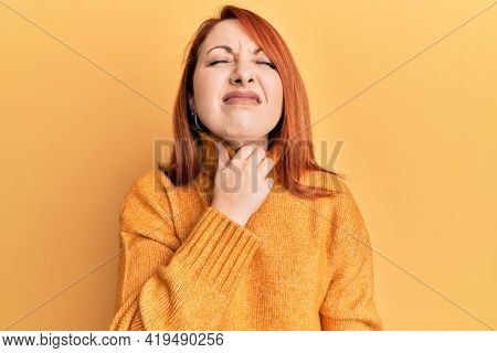 Beautiful redhead woman wearing casual winter sweater over yellow background touching painful neck, sore throat for flu, clod and infection