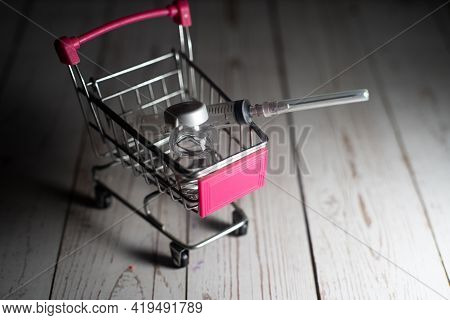 Vaccine Syringe Vial Of Liquid On A Shopping Cart Trolley Showing Online Purchasing Of Medicine From